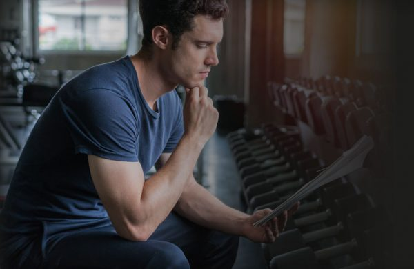Muscular handsome trainer looking at fitness plan on clipboard for working out in the fitness gym